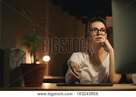 Image of young serious woman designer sitting indoors at night using graphics tablet and computer. Looking aside.