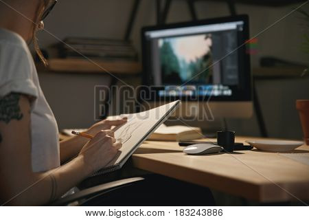 Cropped image of young woman designer sitting indoors at night drawing sketches in album while using computer.