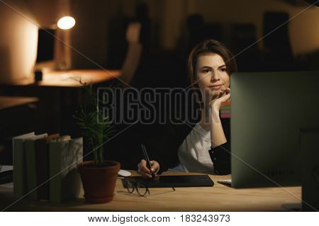 Image of serious young lady designer sitting indoors at night using computer and graphics tablet. Looking aside.