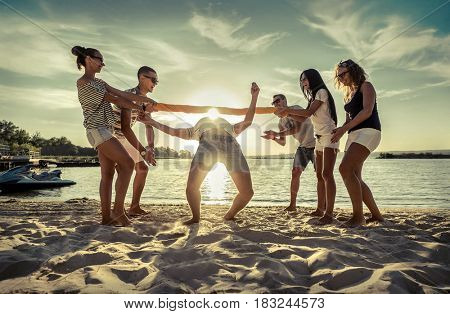 Friends funny game on the beach under sunny sky with clouds at summer day.