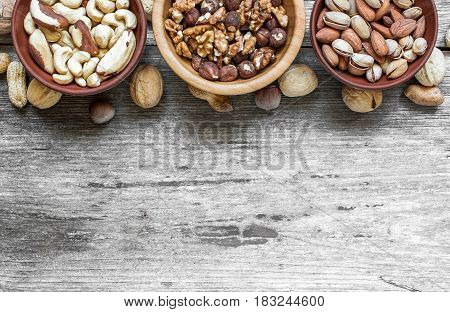 different kinds of nuts bowls over rustic wooden background. top view with copy space