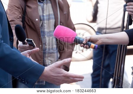 Microphone in focus. Journalists or reporters conducting media interview. News conference.