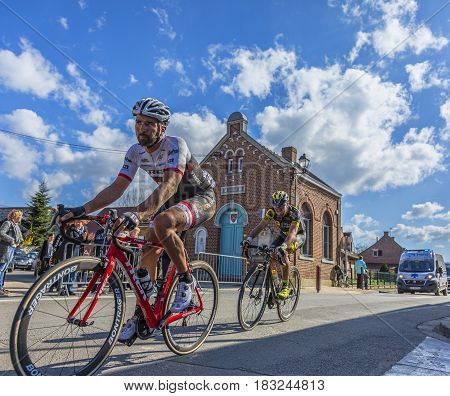 Louvil France - April 102016: Two cyclists riding in front of Louvil Town Hall in France during Paris Roubaix on 10 April 2016.