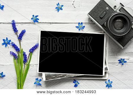 vintage retro camera, blank photo frame and spring blue flowers bouquet on white wooden background. mock up. top view. sprig concept