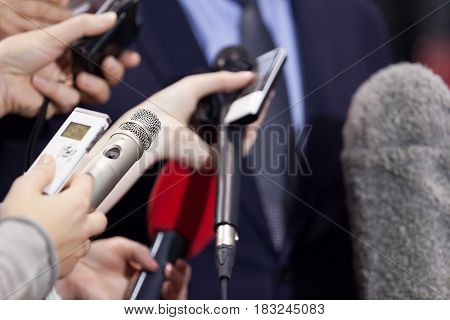Journalists making media interview with businessman or politician. Press conference. Microphones.