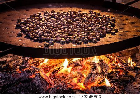 Roasted chestnuts. Big pan on the stove burning. Big pot or pan on the stove burning. The chestnuts are a typical winter food of the Christmas season in Italy.