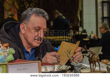 Moscow, Russia - March 19, 2017: Gray-haired antiquarian reads an ancient manuscript in anticipation of buyers at the fair
