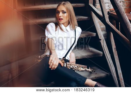 Young Attractive Girl Sitting On Steps In White Shirt With A Saxophone - Outdoor. Sexy Young Woman W