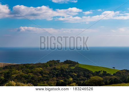 Ocean view with hills green vegetation background and beautiful blue ocean tile travel view