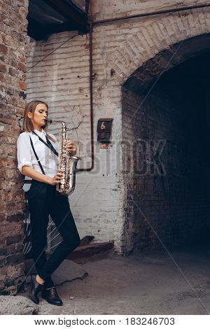 Beautiful Young Girl Plays A Saxophone Standing Near A White Old Wall - Outdoors. Attractive Woman I