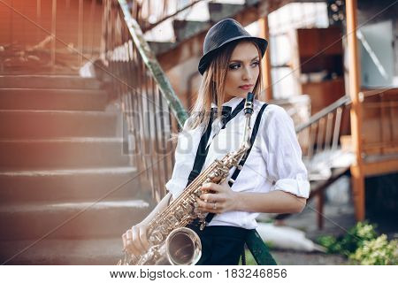 Young Attractive Girl In White Shirt With A Saxophone - Outdoor In Old Town. Sexy Young Woman With S