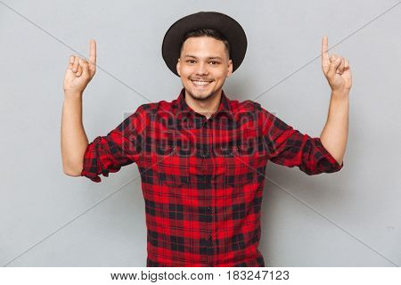 Portrait of a smiling young asian man pointing fingers up isolated on the gray background and looking at camera