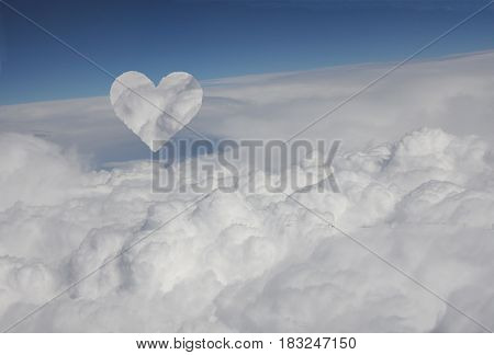 Cloud heart arising from blanket of clouds under blue sky