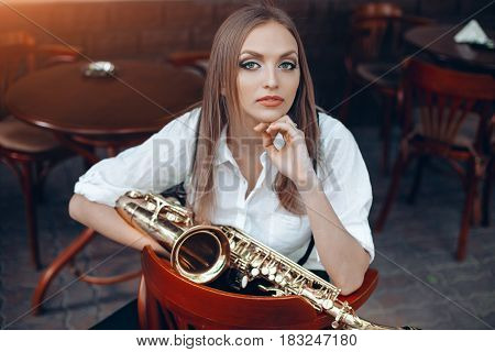 Young Attractive Girl In White Shirt With A Saxophone Sitting On Caffe Shop - Outdoor In Street. Sex