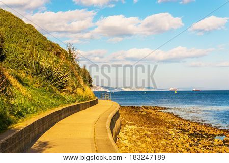 Ocean view from the promenade background ships on the sea and high cliffs sunny day