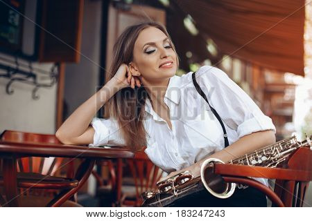 Young Attractive Girl With Close Eyes In White Shirt With A Saxophone Sitting In Caffe Shop - Outdoo