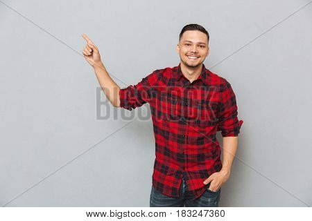 Smilng asian man showing away at empty space with his finger isolated