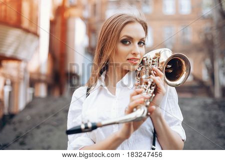 Young Attractive Girl In White Shirt With A Saxophone Standing In Street - Outdoor. Sexy Young Woman