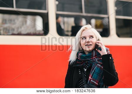 Young smiling blonde woman talking on the phone on the background of the tram. Outdoor portrait