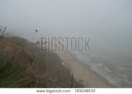 Steep seaside of the Black Sea in dense fog