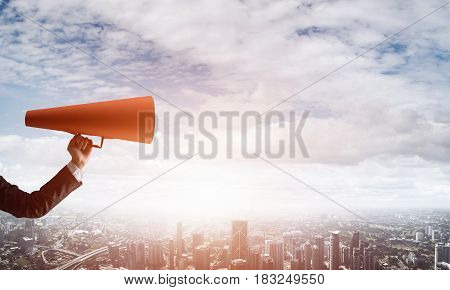 Close of businesswoman making announcement in paper trumpet