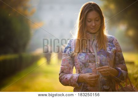 Young sweet woman in love, outdoor backlight. Emotions and femininity. A beautiful woman with a daisy in her hands. She is thinking. Outdoors in a natural setting. Park with green grass.