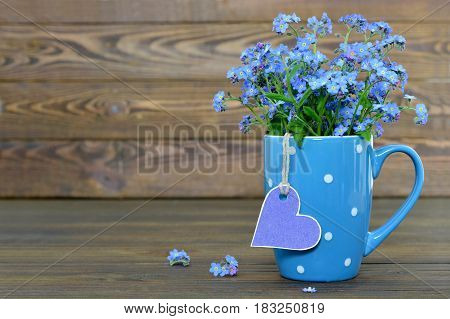 Flowers in the cup and heart shaped tag