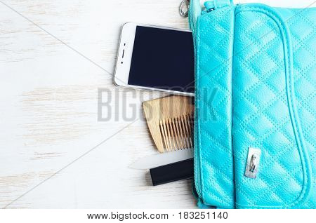Woman's bag and it's content - phone, lipstick, nail file, comb