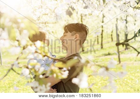 Smiling teenager boy holding baby at blooming cherry blossom trees