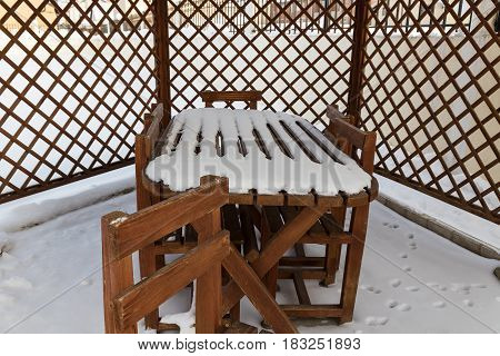 snow covered on wooden table at garden