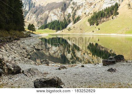 Tranquil scene of lake of seealpsee reflecting the mountain in Alpstein Switzerland