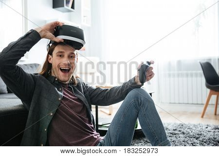 Image of young smiling man sitting at home indoors play games with 3d virtual reality glasses. Looking at camera.