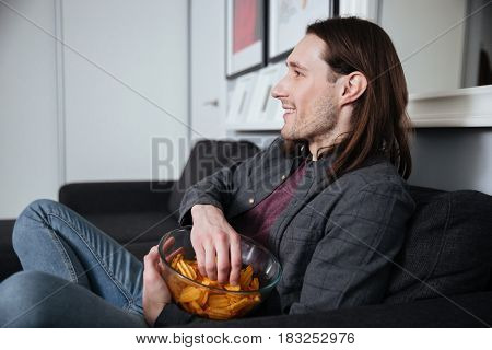 Side view image of young man sitting at home indoors eating crisps. Looking aside while watch TV.