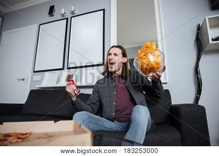 Image of young screaming man sitting at home indoors eating crisps. Watch TV. Holding remote control.