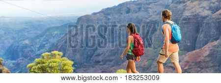 Hikers couple hiking in mountains landscape, banner panorama. Woman and man walking on hike in Waimea Canyon State Park, Kauai, Hawaii, USA. Looking at view happy enjoying healthy outdoor lifestyle.