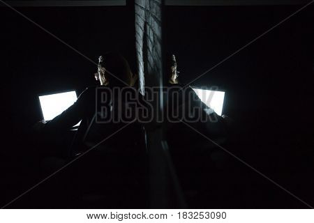Back view image of young concentrated man using laptop computer at home indoors at night near mirror.