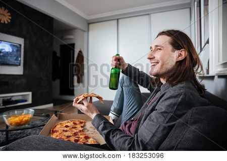 Photo of young happy man sitting at home indoors eating pizza. Watch TV while looking aside.