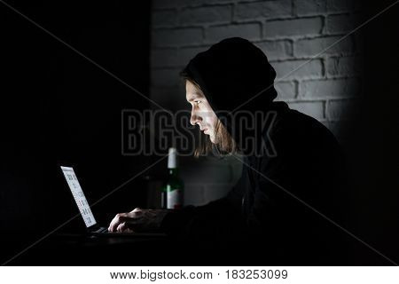 Image of young man using laptop computer at home indoors at night. Looking aside.