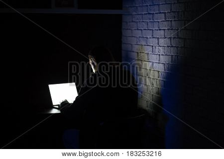 Back view image of young concentrated man using laptop computer at home indoors at night.