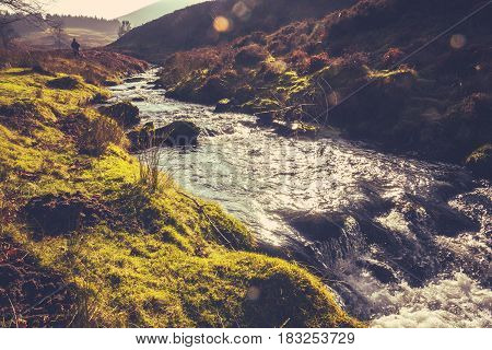 Retro Filtered Photo Of A Man Hiking In The Rugged Scottish Countryside Beside A Stream