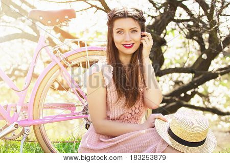 Retro Style. Portrait Of Smiling Young And Beautiful Long-haired Girl In Pink Dress Sitting With Ret