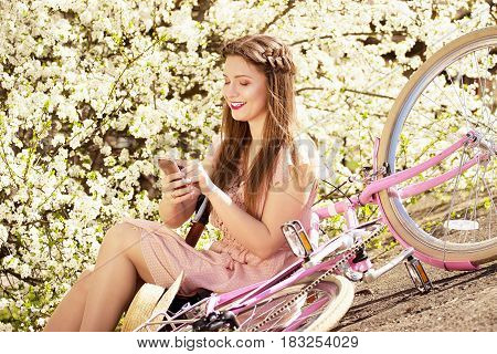 Messaging Outdoors. Beautiful And Young Long-haired Girl In Pink Dress Sitting With Bike And Using H