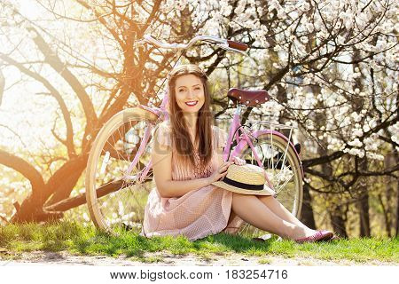 Spring Sunny Day. Smiling Beautiful And Young Long-haired Girl Sitting On Green Grass Near Retro Bik