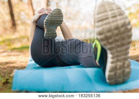 Girl In A Sport Suit, Outdoors, Kneading Her Legs Lying On A Blue Sports Mat