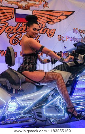 St. Petersburg Russia - 15 April, A fashion model behind the wheel of a motorcycle,15 April, 2017. International Motor Show IMIS-2017 in Expoforurum. Models on motorcycles presented at the motor show.