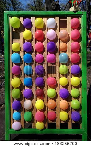 A mobile shooting gallery with multi-colored balloons. Children's entertainment in the city park. Multicolored balloons are in the cell plywood of wall