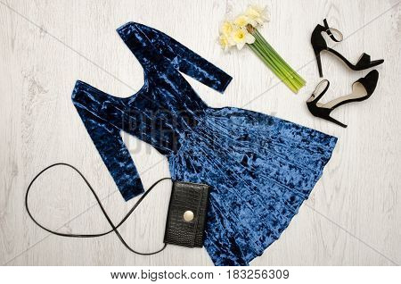 Velvet blue dress black shoes clutch and a bouquet of daffodils. Fashionable concept. Wooden background. Top view