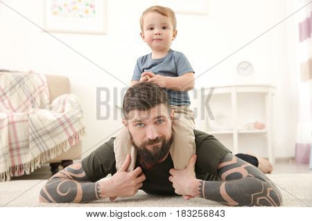 Handsome tattooed young man playing with cute little boy at home
