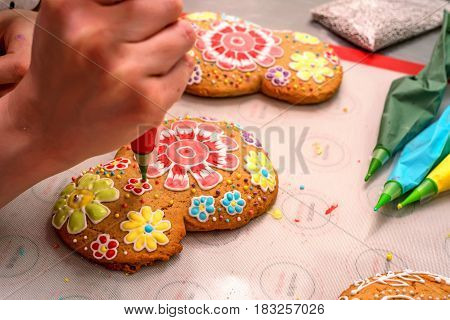 Making holiday gingerbread. Decorating gingerbread with food coloring