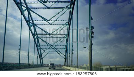 the car goes on the main road at the iron bridge across the Moscow river in the Moscow region on the highway with a speed limit of 90 kilometers per hour
